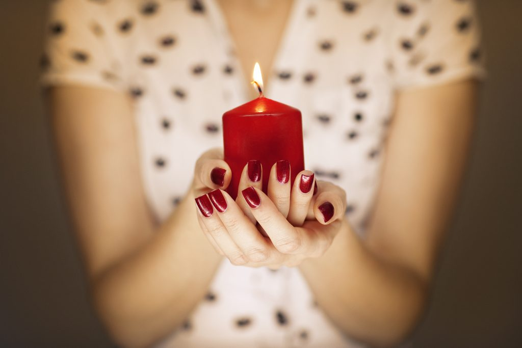 Woman hands holding a candle light