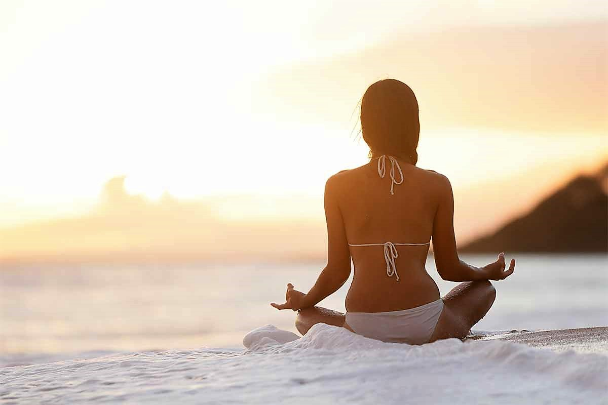 a woman meditating on a beach