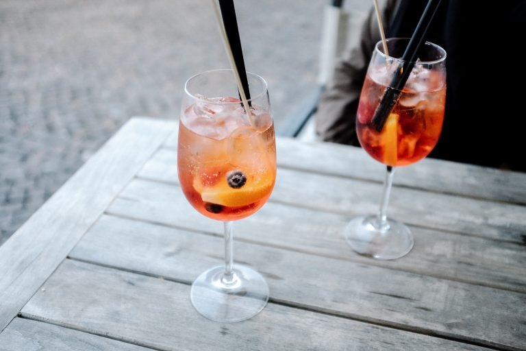 Two summer fruit cocktails sitting on a wooden bench.