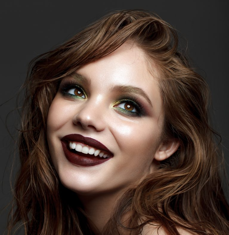 a happy woman wearing red lipstick and green eye shadow