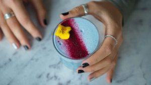 woman with silver nails holding a blue algae cofee