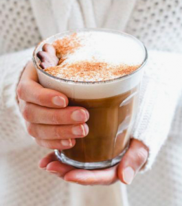 women's hands holding glass cup with hot drink inside