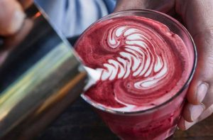 red velvet latte being made in a glass