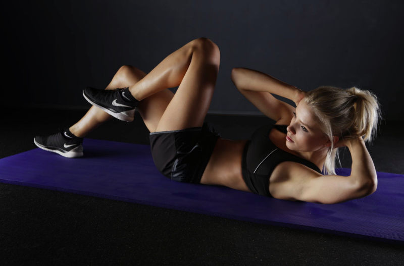 Woman doing alternate crunches on a gym mat. Image from Pexels.