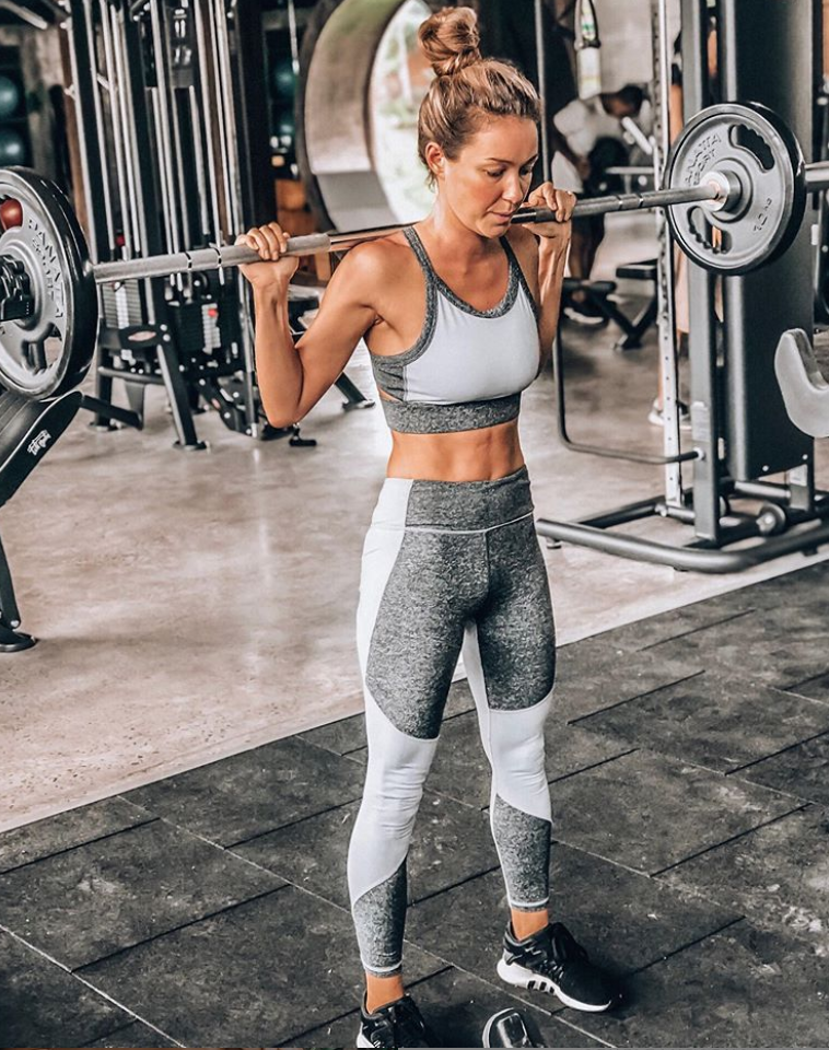 Woman lifting weights at gym.