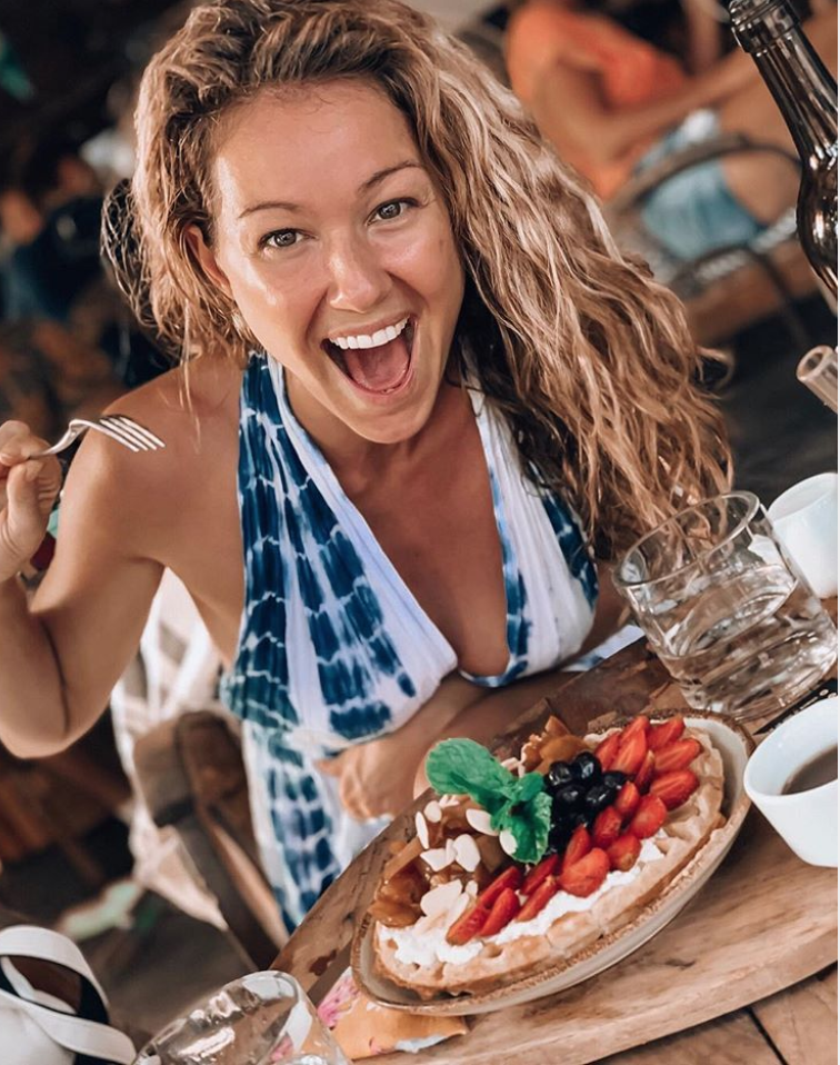 Blonde woman with wavy hair smiling with food in cafe.