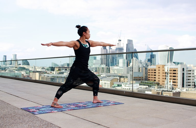 woman doing yoga on a rooftop