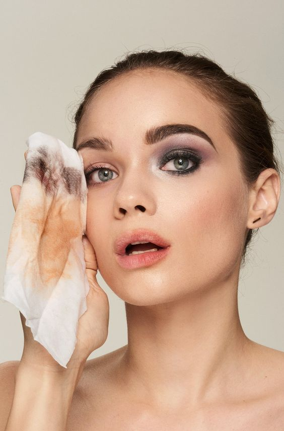 Woman removing makeup with makeup remover wipes
