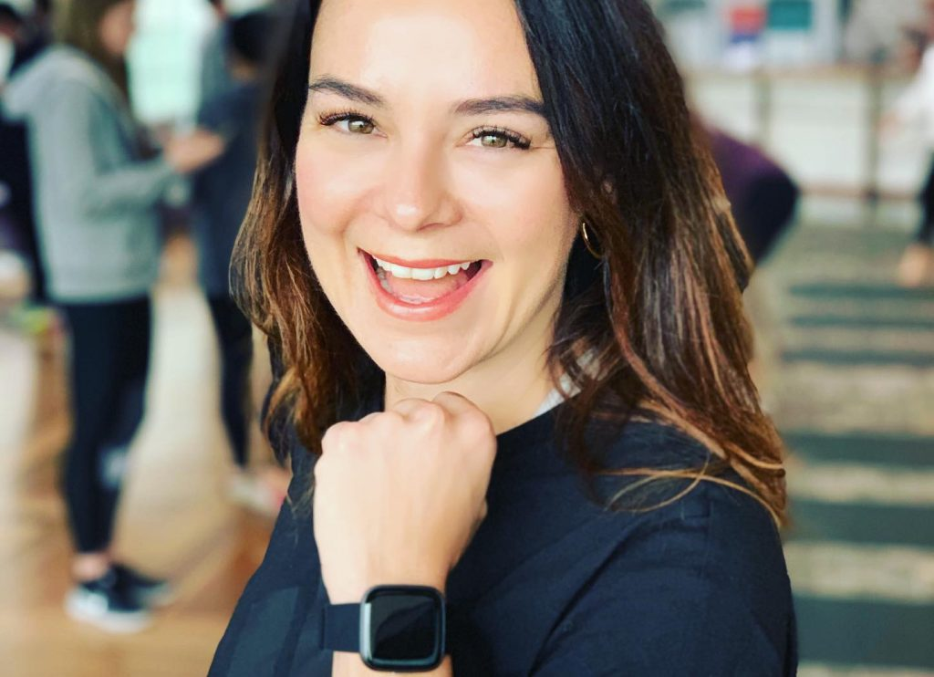 brunette woman smiling at camera with black fitbit smartwatch on her wrist