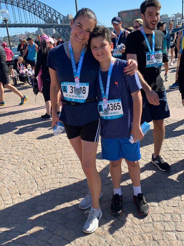 mother and son under the harbour bridge in sydney wearing medals after a marathon