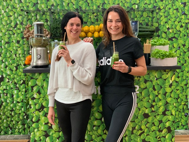 two womene in front of plant. wall drinking smoothies