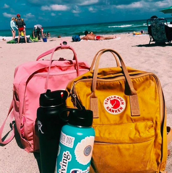 Hydroflask and Fjallraven Kanken backpack at the beach.
