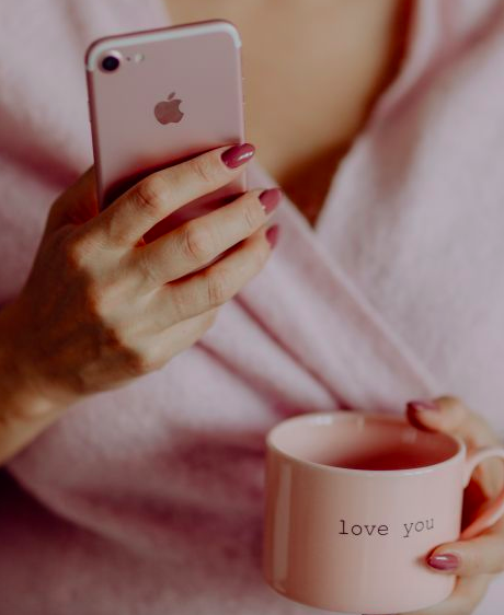 Girl holding pink phone with pink mug.