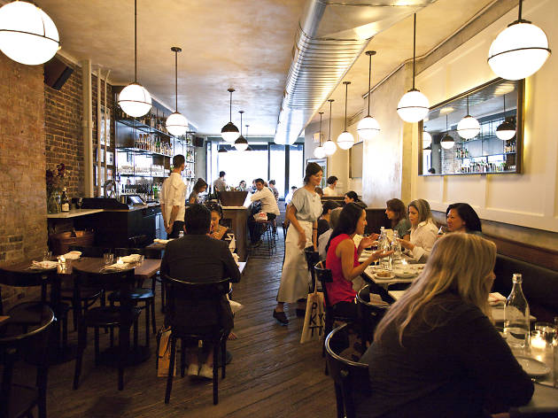 Crowded thin restaurant with polished floor spa small wooden tables.