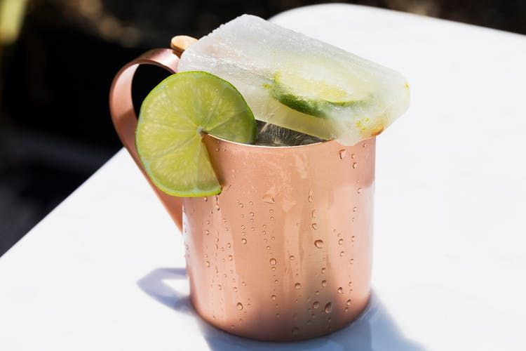 Moscow Mule popsicle perched on top of rose gold metal mug with lime slice wedged on top.