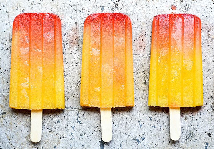 Three Tequila Sunrise Popsicles in a row.