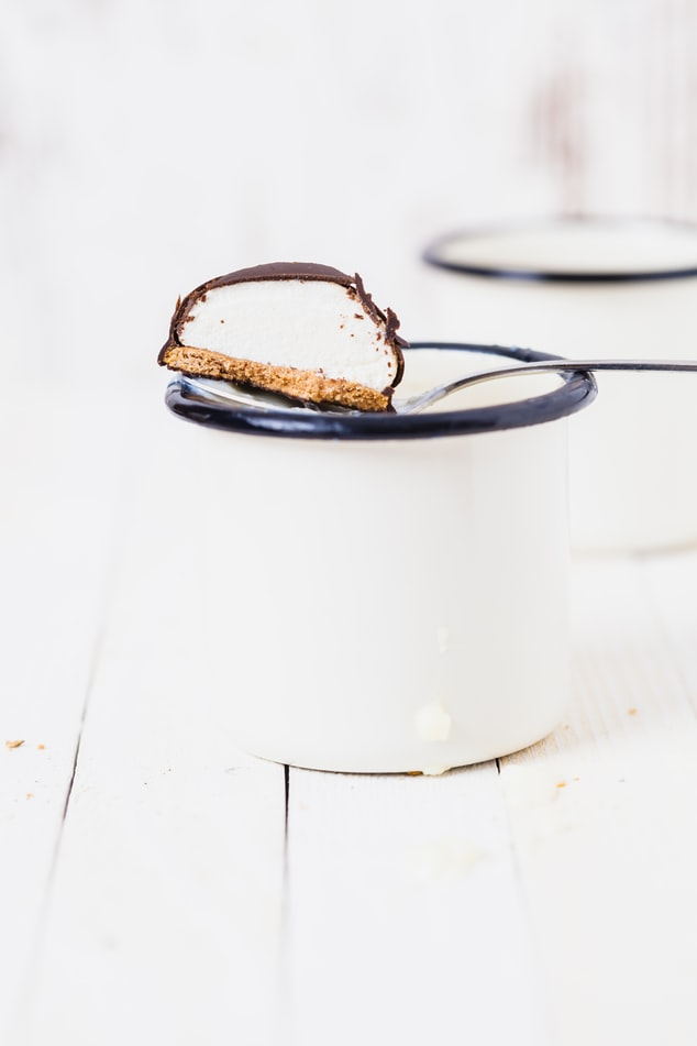Marshmallow biscuit with chocolate coating cut in half on spoon over white metal cup with navy rim