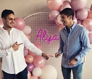 two men smiling at each other with pink and white balloons
