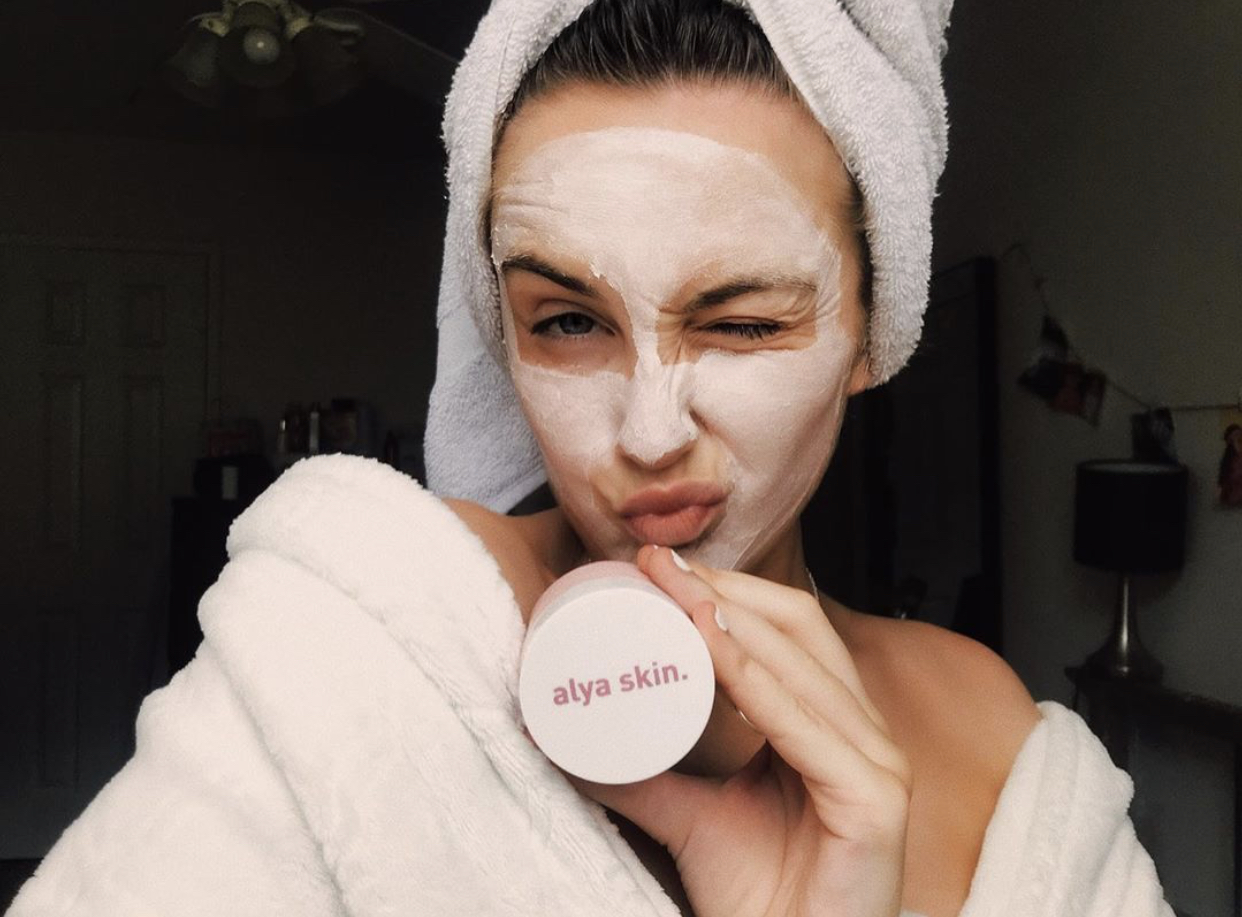 woman wearing face mask holding alya skin product
