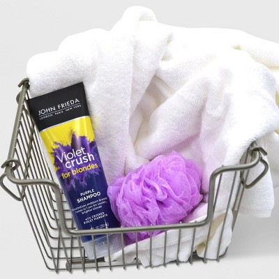 John Frieda Violet Crush Purple Shampoo in washing basket with purple loofa and white fluffy towel