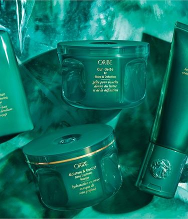 Oribes New Moisture and Control Collection in a flatlay with emerald green backdrop.