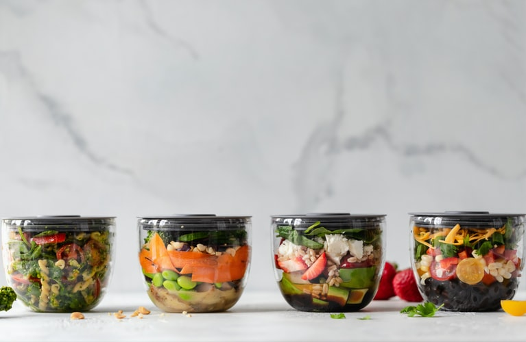 Four closed containers of vegetables and healthy food.