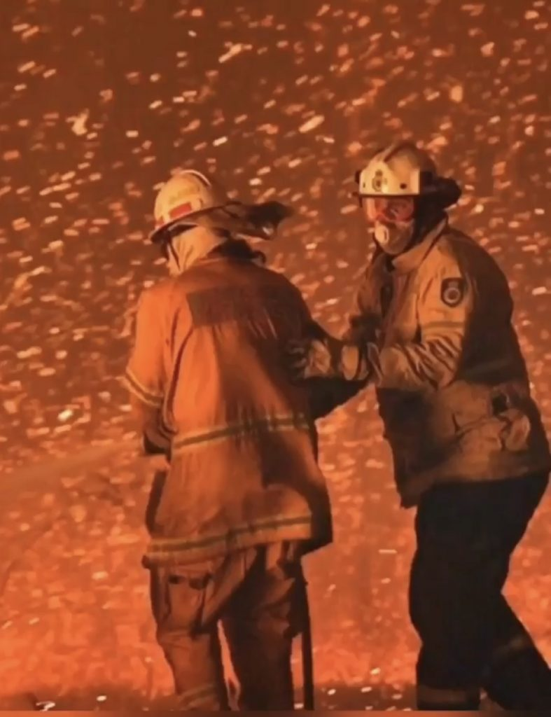 Fire fighters with back to camera with orange embers falling from the sky