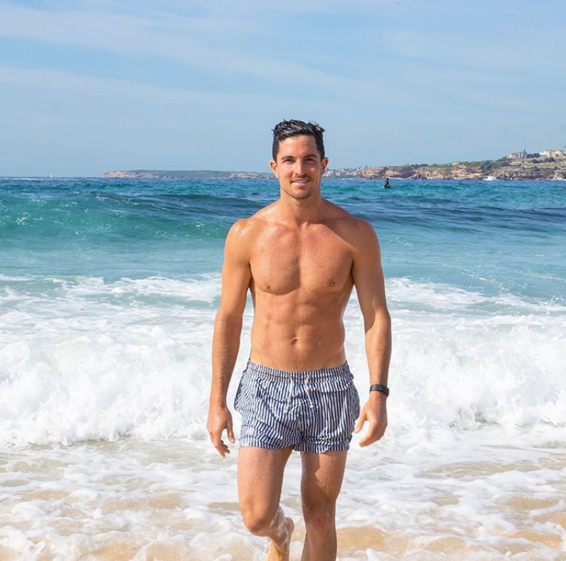 Man on the beach in front of waves wearing light blue shorts