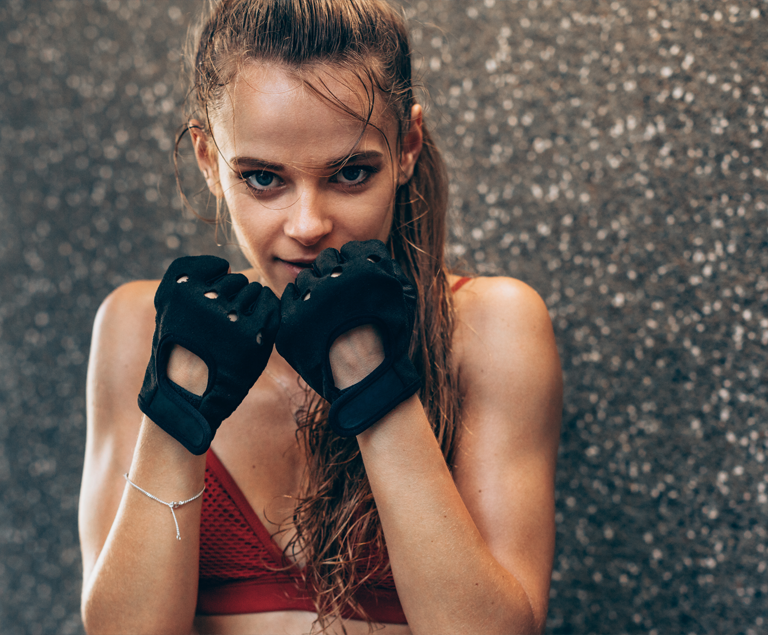 Brunette with long ponytail in boxing gloves and red crop top.