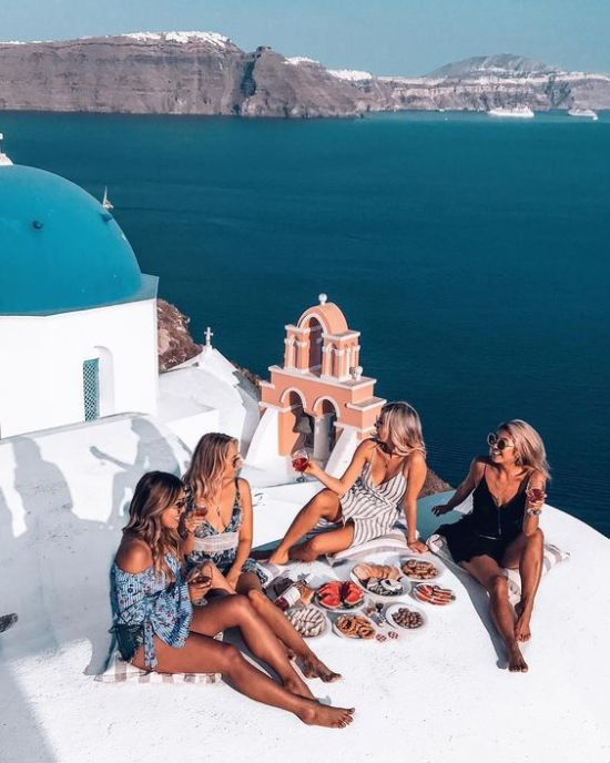 Four girls eating a picnic in view of the Santorini coastline.