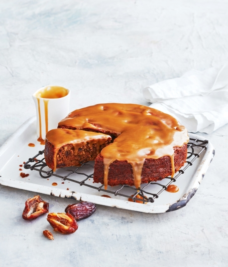 orange colour cake dropping in sauce with a slice cut out on a white square plate