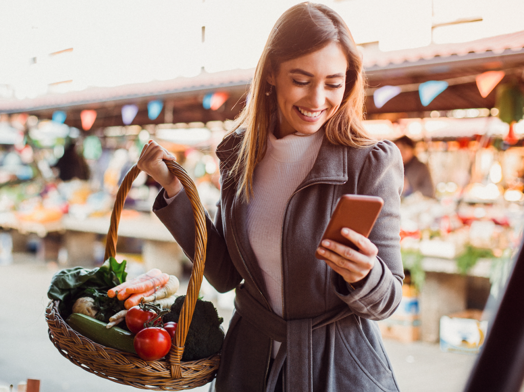 Young woman in thick grey jacket in supermarket with basket of groceries