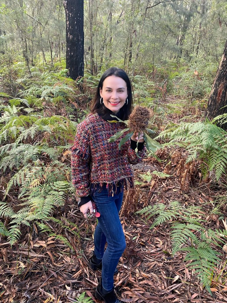 Woman holding a Banksia plant in the australian bush wearing blue jeans and red and orange top