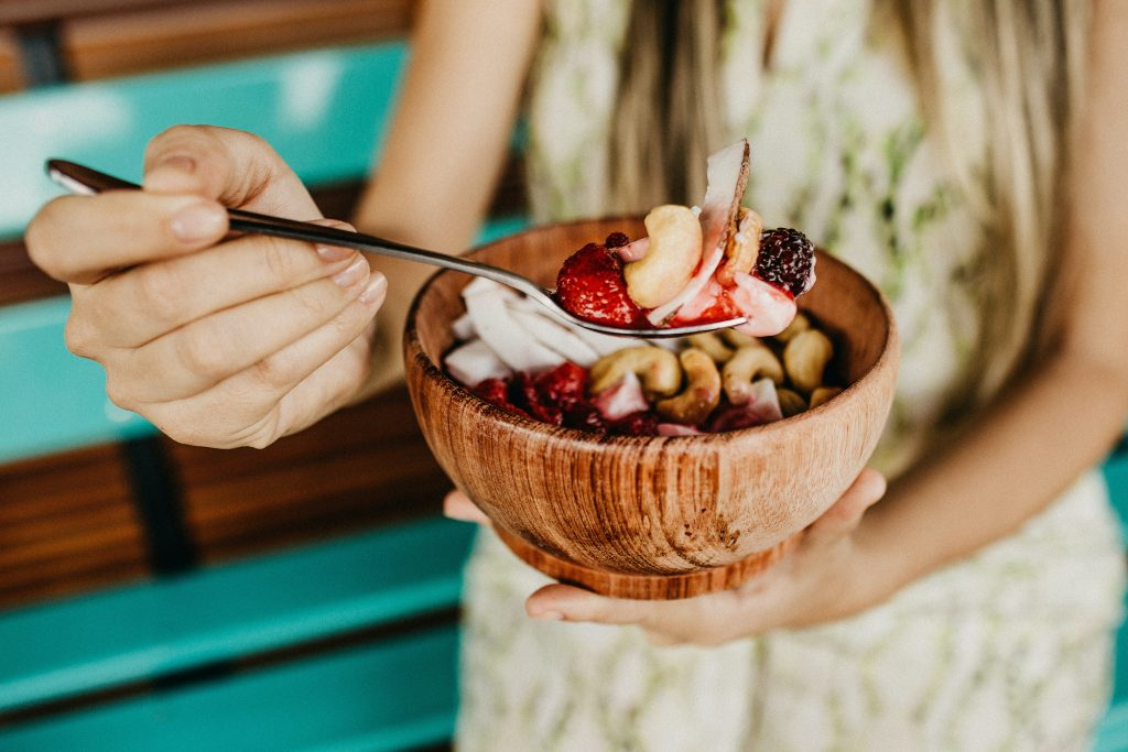 person holding smoothie bowl in a coconut bowl