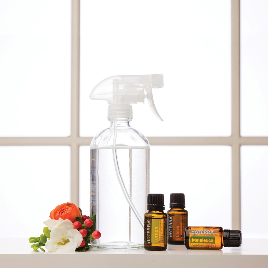 Spray bottle on table in front of window with dōTERRA essential oil bottles