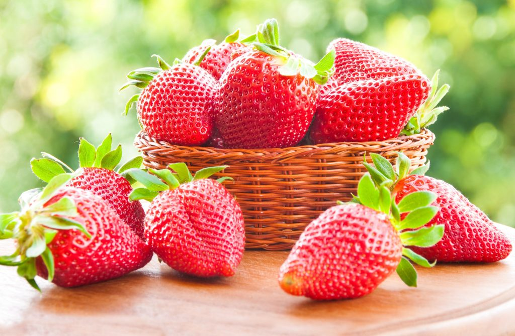 Punnet of strawberries on table and in woven basket