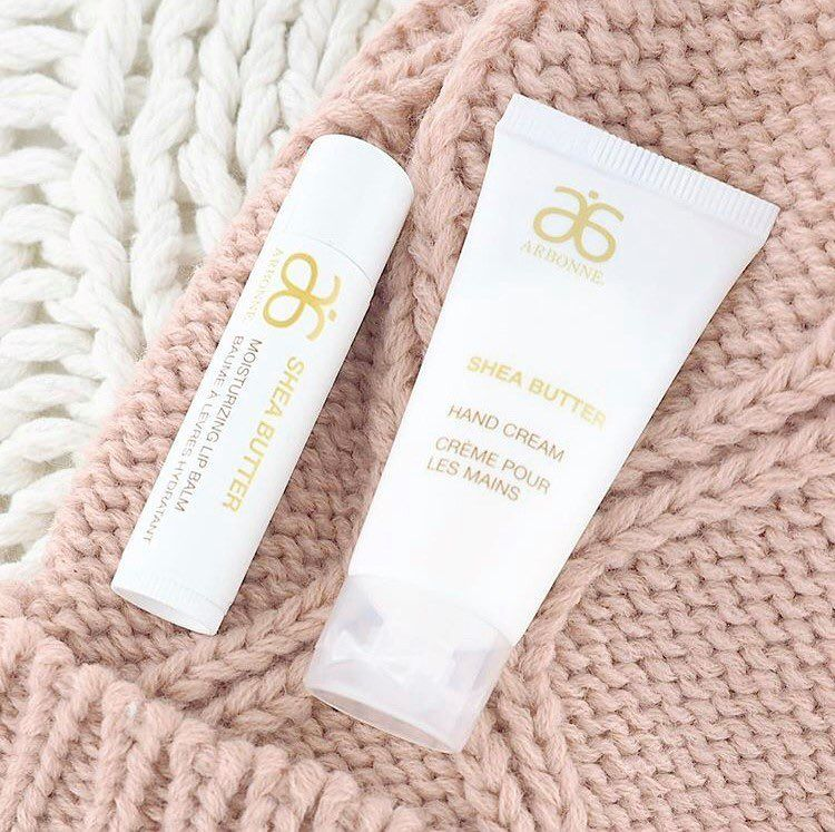 Arbonne Shea Butter Hand Cream flatlay on sweater - image from pinterest