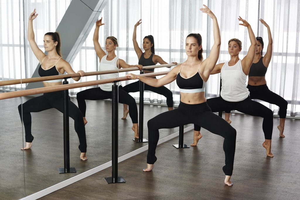 Three women doing barre exercising in front of mirror.