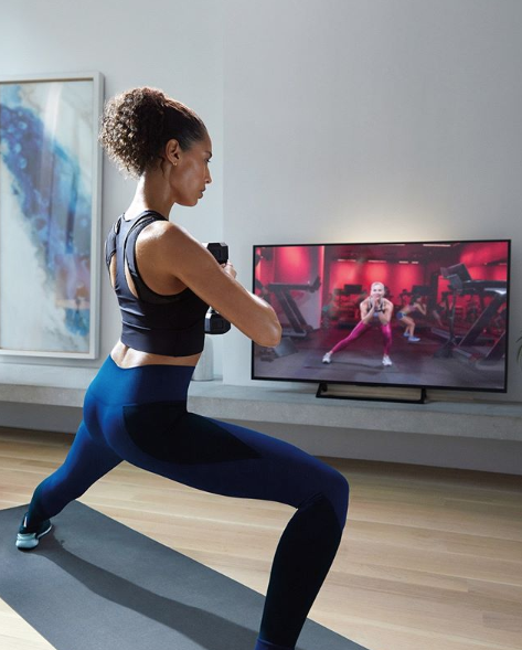 Woman exercising in front of instructional video on television screen.