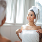 Girl in towel looking in mirror
