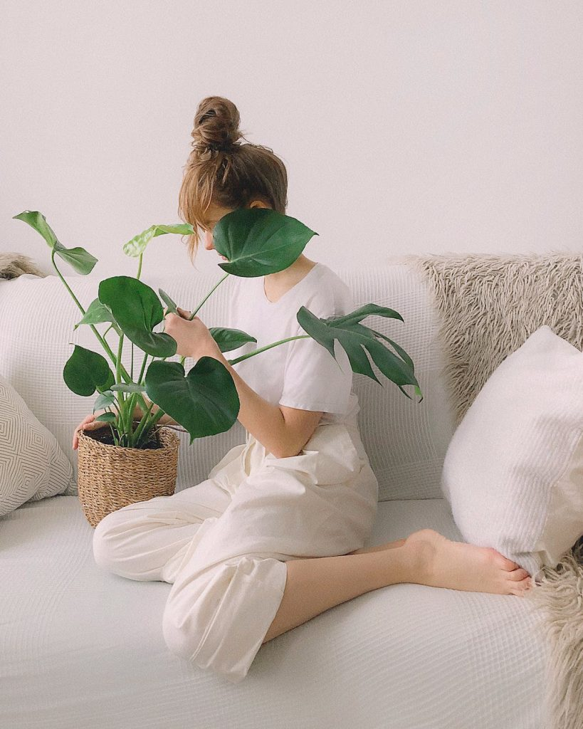 woman with green monstera plant