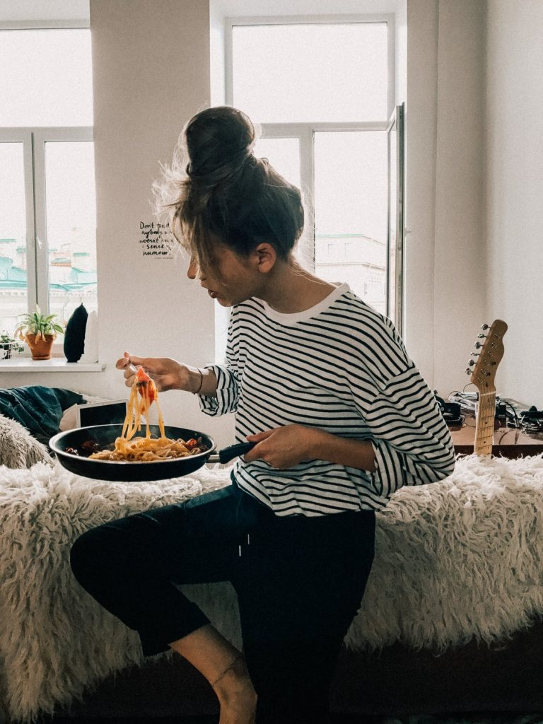 woman cooking at home and eating pasta from a pan
