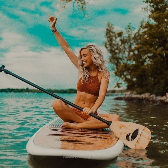 A women is sitting cross-legged on a paddle-board. Image found on Pinterest.