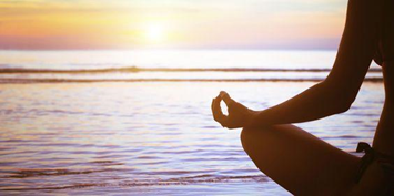 Making Meditation Mainstream. A woman meditating on the beach an sunrise.