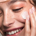 Woman with freckles applying face cream