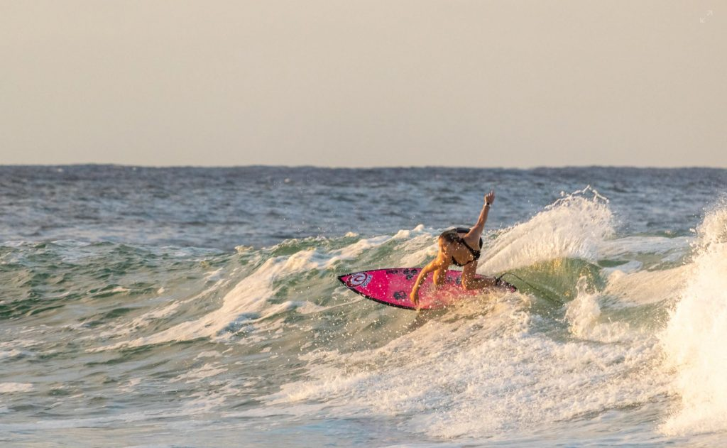A female surfer on a pink board catching a wave.