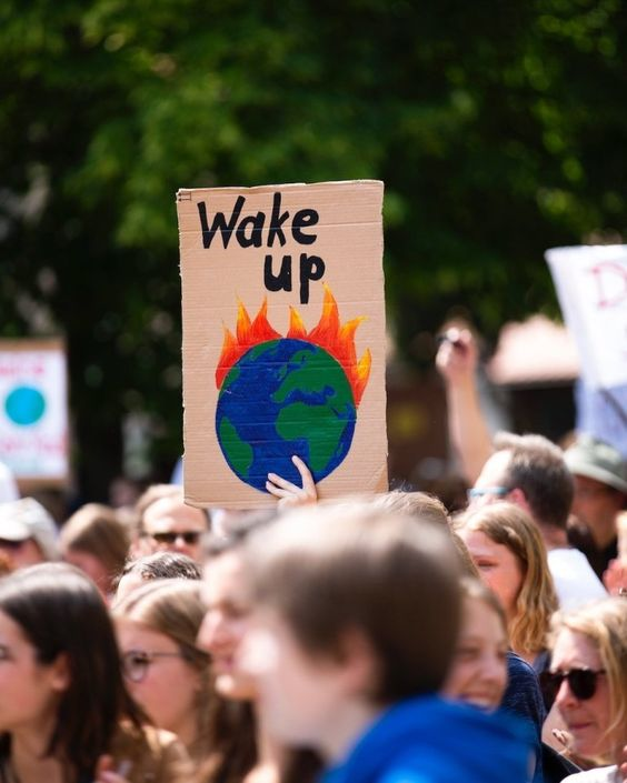 A 'Wake Up' poster at a climate change rally depicting planet Earth burning/ on fire.
